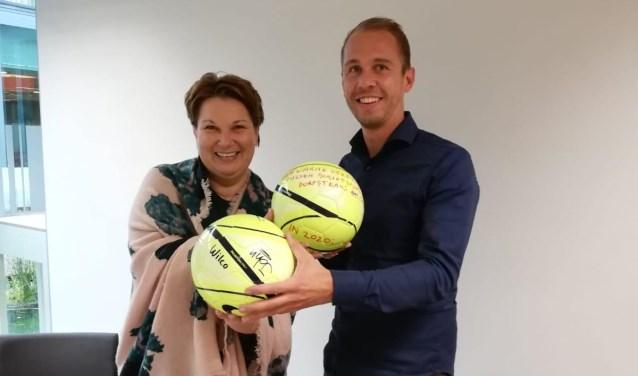 Wethouder Chantal Broekhuis en buurtsportcoach Ruben Buist wisselen ballen uit.