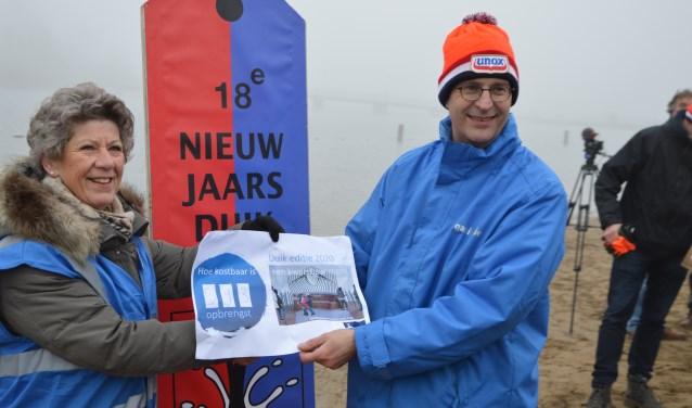 Lida van der Marel (Stichting Herdenkingsmonument Houten) ontvangt de cheque uit handen van Erik de Groot (Stichting Nieuwjaarsduik Houten).