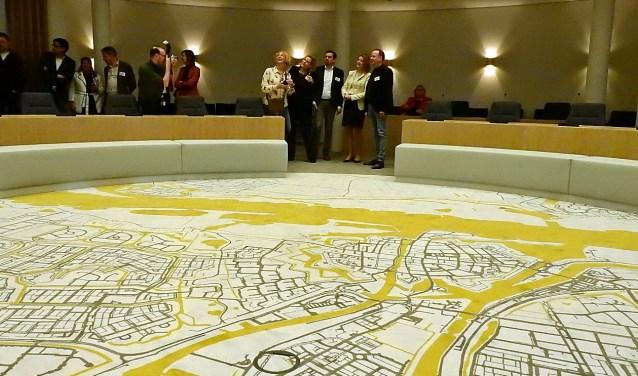In de vernieuwde raadzaal ligt een tapijt met de plattegrond van de stad