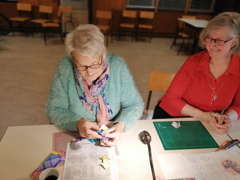 Mien Krauweel (links) in de weer met origami. Privé © BDU Media