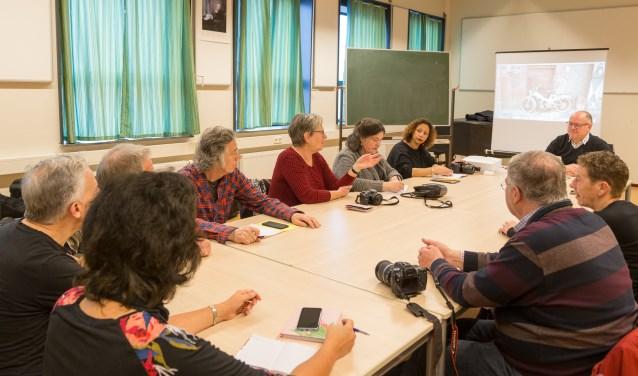 Deelnemers aan de lessen fotografie bespreken hun gemaakte werk