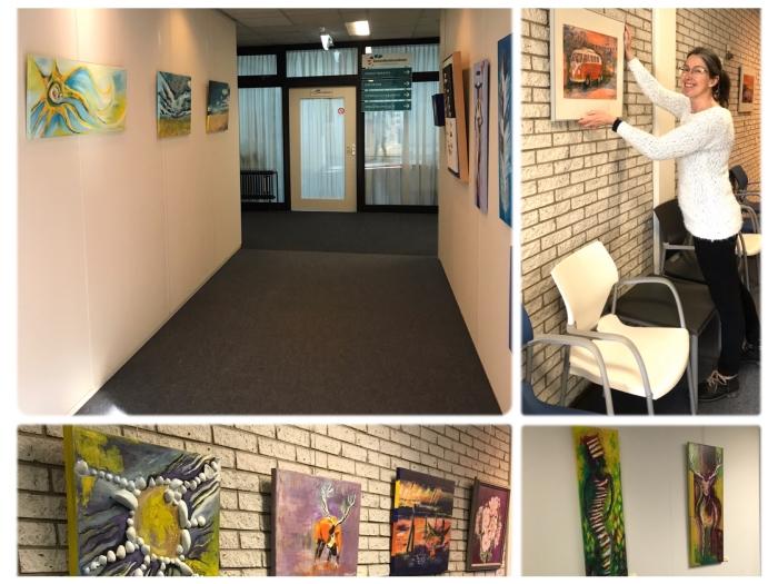 Kunstenares Beatrice Martinetz bij het ophangen van de schilderijen in de wachtruimtes van Gezondheidscentrum Veldhuizen