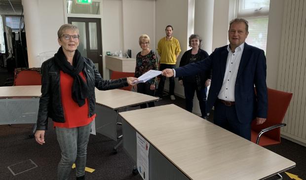 <p>Het aanbieden van de handtekeningen voor een eigen buurthuis aan wethouder Jan Nederveen.&nbsp;</p>