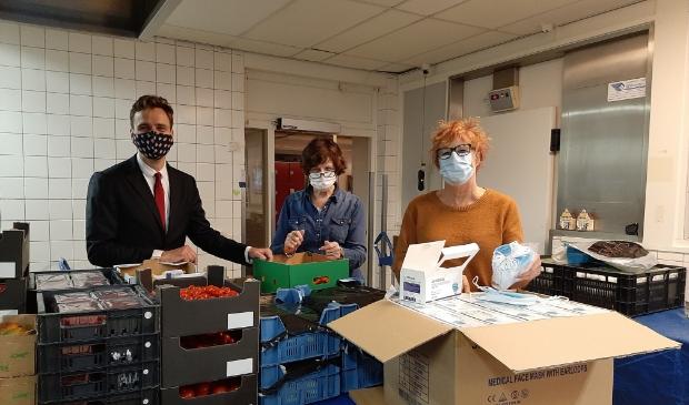 <p>Vanaf links: wethouder Marijn van Ballegooijen, Marja Ernste van de Voedselbank en raadslid Stieneke Kruijer met de doos vol mondkapjes.&nbsp;</p>