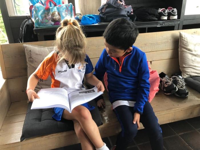 F-pupillen samen verdiept in het jubileumboek