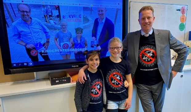 <p>Saskia en Anna showen samen met de wethouder het door hen ontworpen T-shirt.</p>