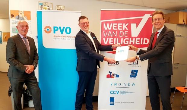 <p>Burgemeester Tjapko Poppens overhandigt PVO map aan Kees Cats. Links Maarten Duijn van het CCV.</p>