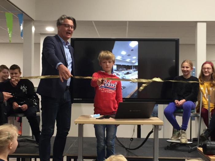 Bestuurder Rob Boerman (KS Fectio) en leerling Mart Hoefnagels verrichten samen de symbolische heropening van de vernieuwde aula van de Barbaraschool.