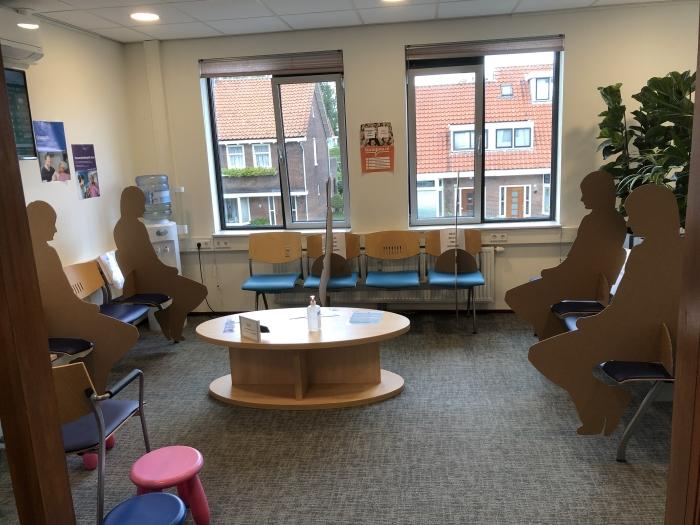 Kartonnen poppenin de wachtkamer van Huisartsenpraktijk Amstelwijck. Die zijn geplaatstom ervoor te zorgen dat bezoekers niet dicht bij elkaar kunnen zitten.