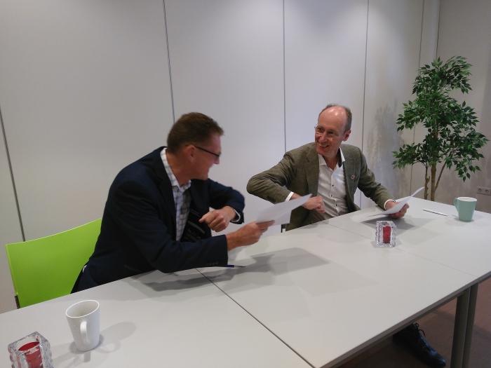 Paul Nagtegaal en Lex Hoefsloot doen elleboogstoot na ondertekening samenwerkingsovereenkomst