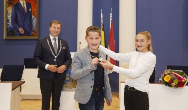 <p>Maud Smit, de vorige kinderburgemeester, hangt Hugo Wennekes de keten om.</p>