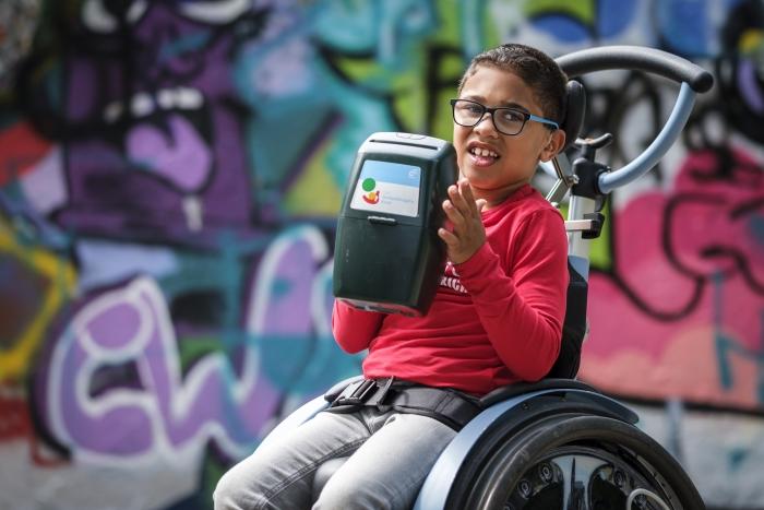 kind met een beperking met collectebus van het Gehandicapte Kind