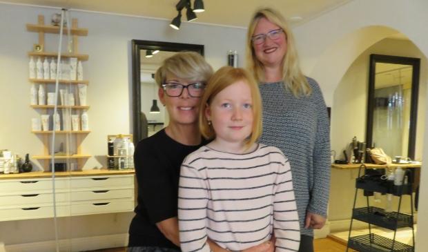 <p>De trotse Isis met haar korte haar, kapster Monique en moeder Mieke (rechts).</p>