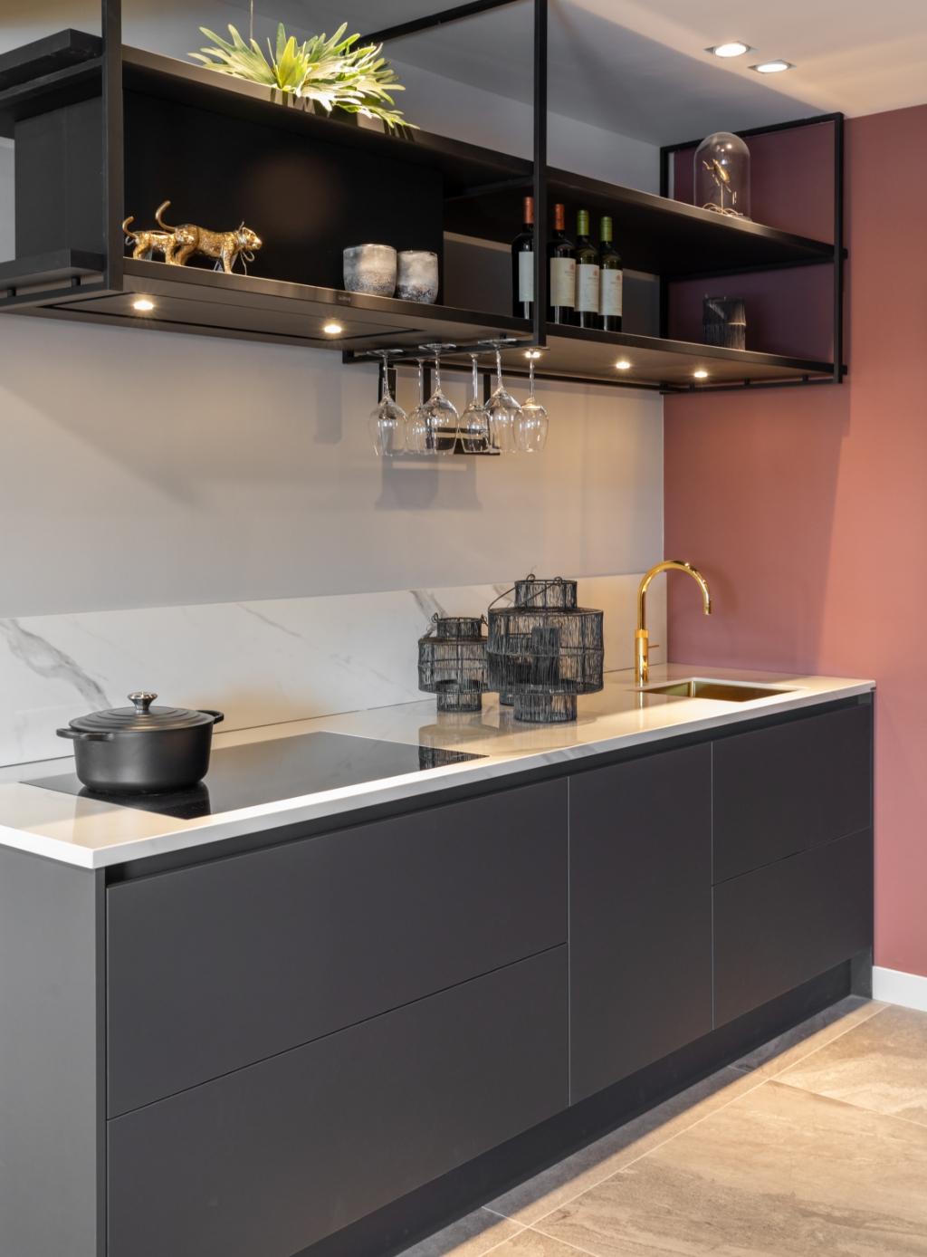 <p>Antracietkleurige greeploze keuken met marmerlook werkblad. Om de keuken een eigentijds stempel te geven is gekozen voor een opvallende goudkleurige Quooker.</p> Nanette de Jong Fotografie © BDU media