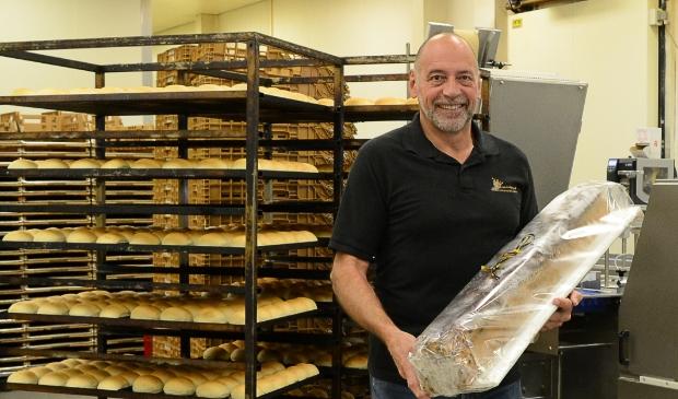 <p>Harrie van Looijengoed met een meter krentenbrood in de ambachtelijke bakkerij.</p>