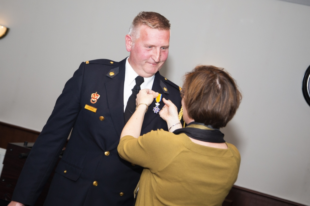 Reijer Brons krijgt de koninklijke onderscheiding opgespeld door zijn echtgenote. Erik van 't Land © BDU media
