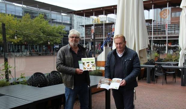 <p>Robert Mathijsen (links) en Michel Becker tonen op een gesloten terras het boek vol recepten van de lokale chefs.</p>