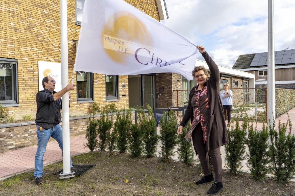 Hospice De Cirkel is vanaf 12 november officieel open. Samen met vrijwilliger Henry Stok hijst coördinator Iris van Putten de vlag.  JC Brouwer Media © BDU media