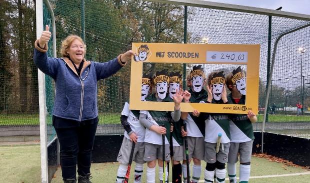 Jongens Shinty JF2-1 geven cheque aan Linda Platvoet van de Voedselbank Utrechtse Heuvelrug