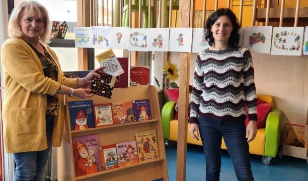 Ellen van Eijmeren (Bibliotheek AanZet) en Leny de Bruin (Wasko Kinderopvang) met het keurmerk Boekstart bij de nieuwe boekenkast waarbij de boekjes goed zichtbaar en op ooghoogte staan.