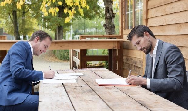 <p>Ronald van Bemmel, directeur Softs (links) en Eelke Kraaijeveld, wethouder Duurzaamheid tekenen de overeenkomst</p>