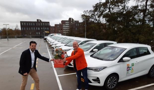 Martijn van Kampen(links) namens Renault Nieuwendijk een boeket bloemen aan Bas Rouendal van de gemeente bij de aflevering van 14 nieuwe Renaults.