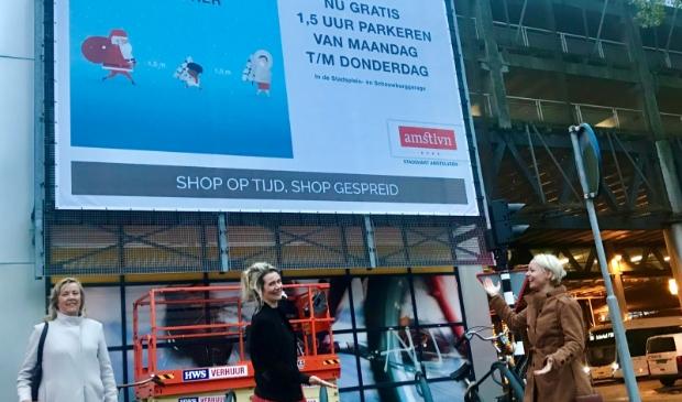 <p>Anneke van Dijk, Marlou Molenaar en Floor Gordon bij bord met oproep om op tijd inkopen te doen.</p>