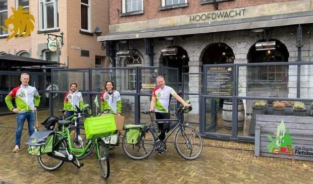 <p>Marcel Herrewijn van de Fietskoerier poseert samen met Pien Bogaard, Rene Joosen en Monica de Ras voor de Hoofdwacht</p>