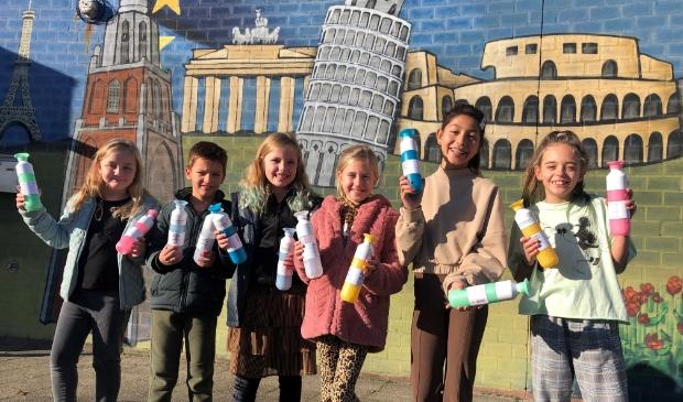 Leerlingenteam neemt waterflessen in ontvangst