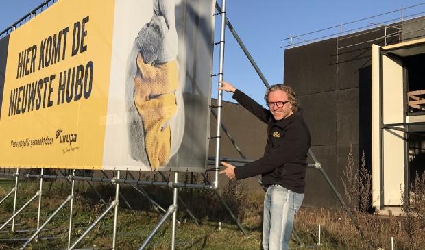 Roland Hartkamp bij het bord langs de snelweg A1 dat de komst van Hubo Hoevelaken aankondigt.