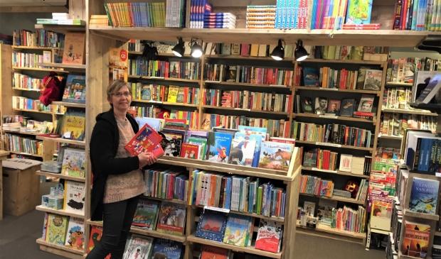 Mieke vd Boomgaard trots bij één van de nieuwe boekenkasten