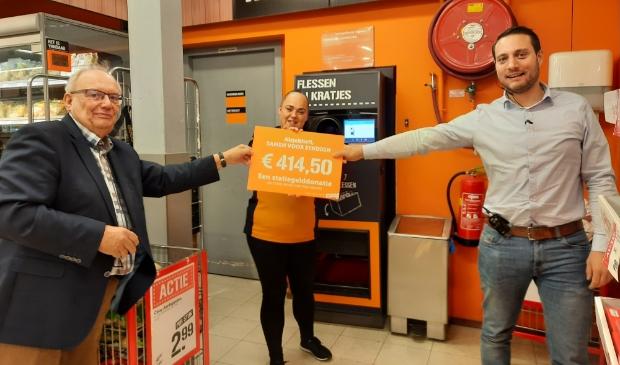 <p>Bart Bruggeman, voorzitter van Samen voor Syndion (links) neemt onder toezicht oog van Daisy, client bij Syndion en werkzaam bij Coop, de cheque in ontvangst van supermarktmanager Tim Walg.</p>
