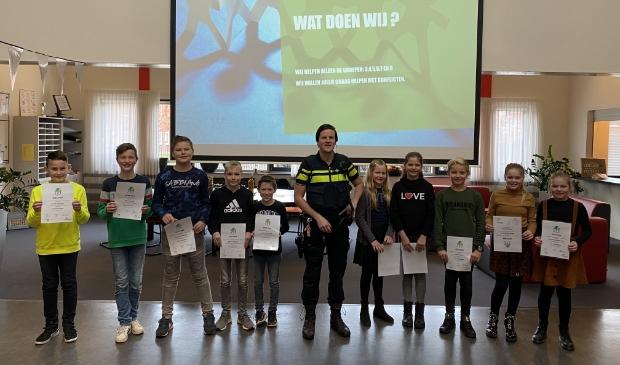 Wijkagent Boerendans op de foto met de 10 leerlingmediatoren.