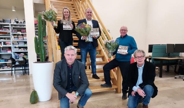 Peter Beijer (links) en Lex Bergers reikten de eerste boeken uit aan Marloes en Martijn Martens en Jaap van den Broek