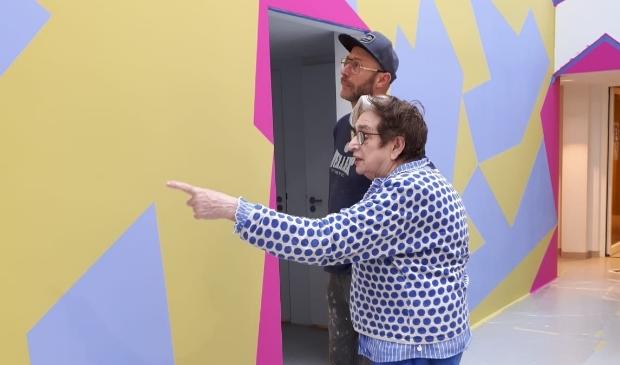 Henriëtte van 't Hoog bekijkt de door haar ontworpen muurschildering in de entree van het Mondriaanhuis.