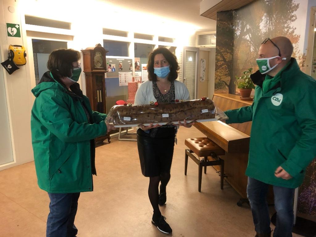 Raadsleden Cora van Wijngaarden en Jan-Willem Nuis bieden een krentenbrood aan Aart van Wijngaarden © BDU Media