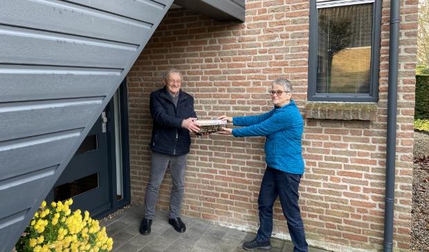 Bert van Rossum overhandigt staven en kaarten aan Wies Maas, beiden Zonnebloemvrijwilliger