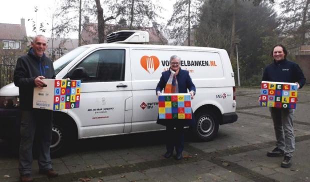 Ron van Zeggeren (bestuurslid Foundation) en Janco Romeijn (Mondial R. Vlot & Zn. Verhuizingen) overhandigen de Speelgoededoelendozen aan Anke van Veen van de Voedselbank.