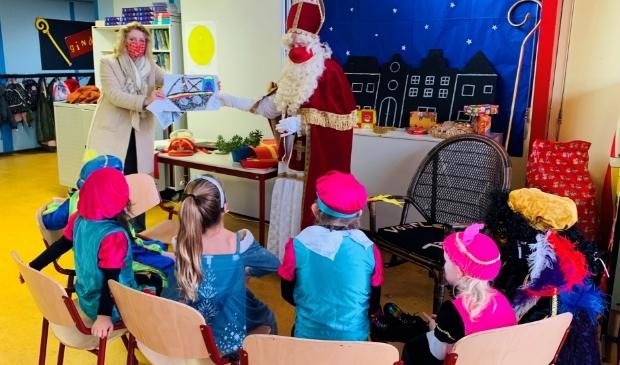 Burgemeester Reinie Melissant-Brienen overhandigt de tekeningen van de Gorinchemse kinderen aan de Sinterklaas