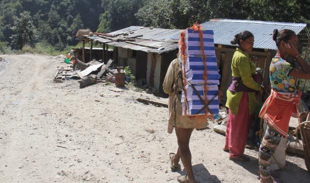 Schoolmiddelen worden te voet naar afgelegen gebieden gebracht