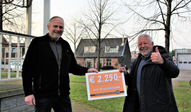 <p>Een stralende Hans de Bats (r) krijgt uit handen van Jacco Groen de cheque overhandigd.</p>