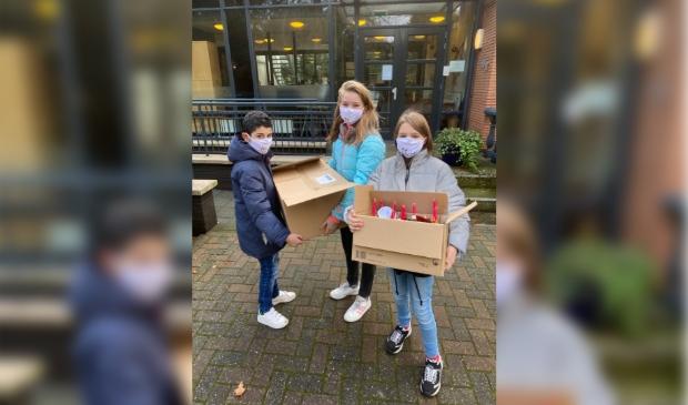 Marwan, Tessa en Eline van de Valkenheuvel met de dozen vol kerststukjes.