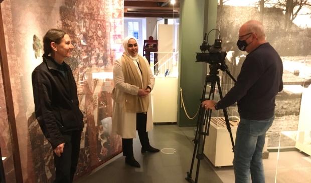 Ely Hackmann filmt kunstenares Linda Verkaaik en wethouder Nadya Aboyaakoub bij de start van de expositie 'Van de wieg tot het graf' in Museum Nijkerk.