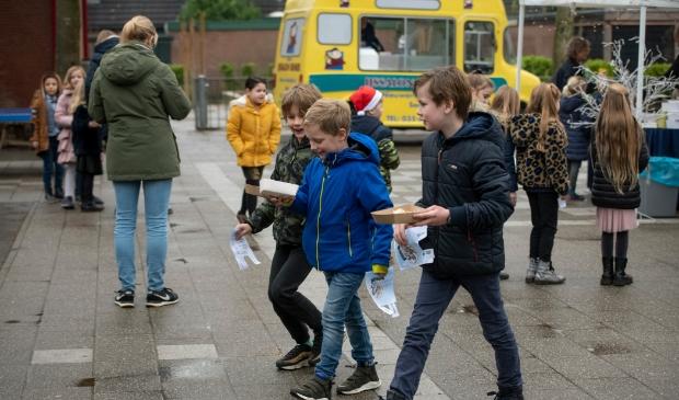 Kinderen gaan met hun lekkers naar de klas.