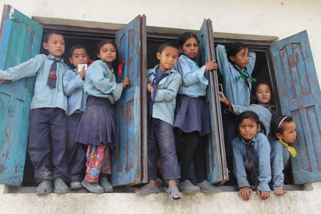 Kinderen poseren in de pauze in de opens schoolramen Stichting Hart4onderwijsNepal © BDU