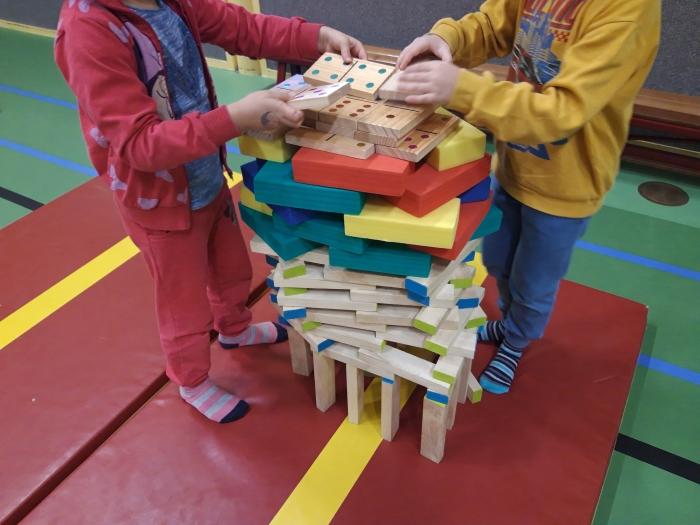 Kinderen bouwen mooie torens met elkaar.