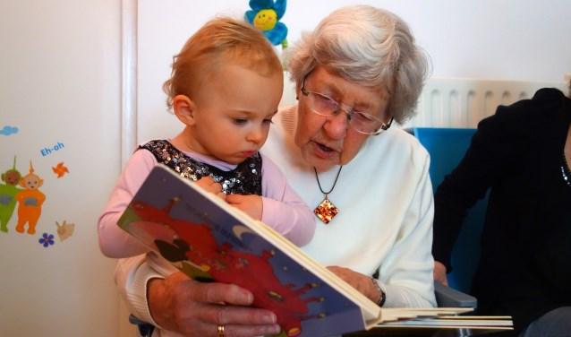 Voorlezen, puzzelen, een praatje. Contact tussen senior en peuter.