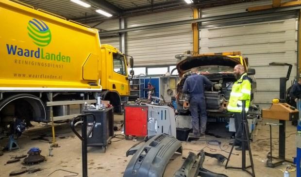 Hans van den Brule kijkt toe terwijl een van de monteurs werkt aan een auto van reinigingsdienst Waardlanden.