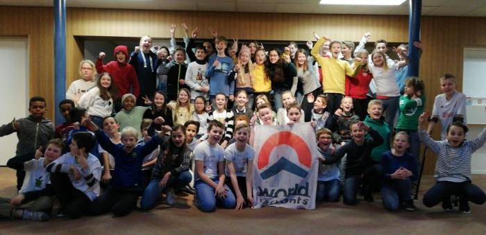 De groepen 7, 8a en 8b van de Koepelschool met de vlag van World Servants
