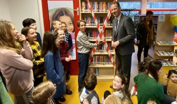 Voorleeskampioen Lucas en wethouder Berkhout knippen samen het lint door en openen daarmee de bibliotheek.